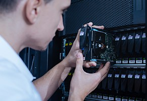 technician swapping out hard drives in rack modular data storage system