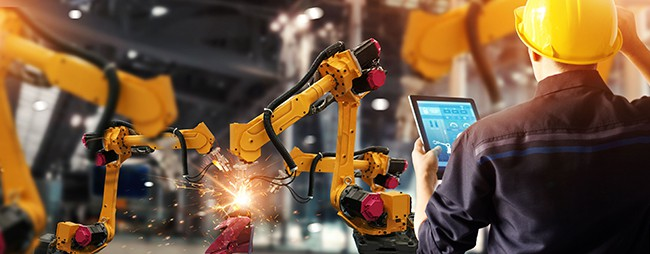 robotic welding with man in hard hat controling them from a tablet